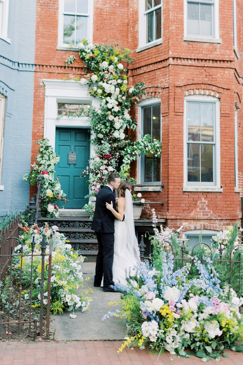 brick townhouse decorated with flowers and greenery trailing up the wall above the door