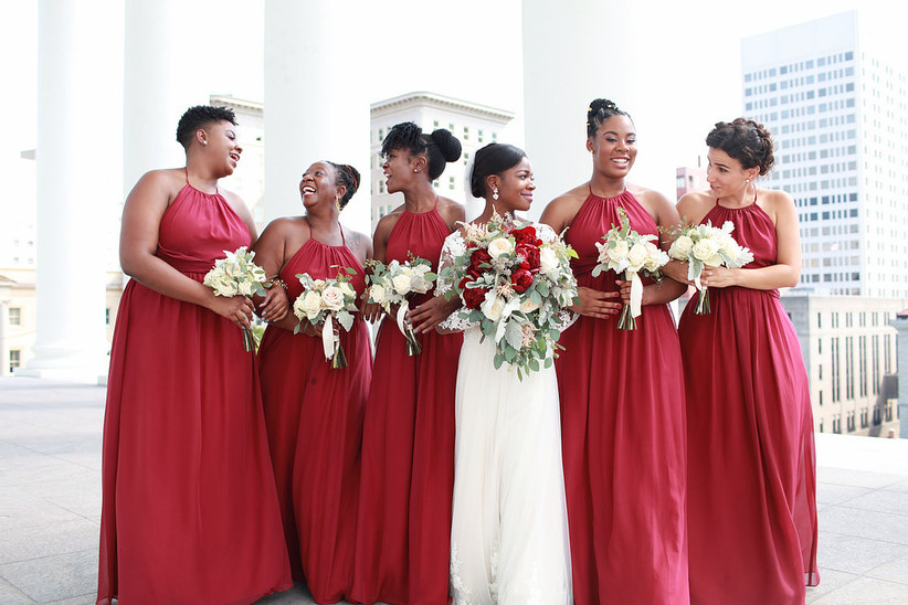 black bride with her bridesmaids wearing long red dresses walking through city scene carrying white rose bouquets with greenery