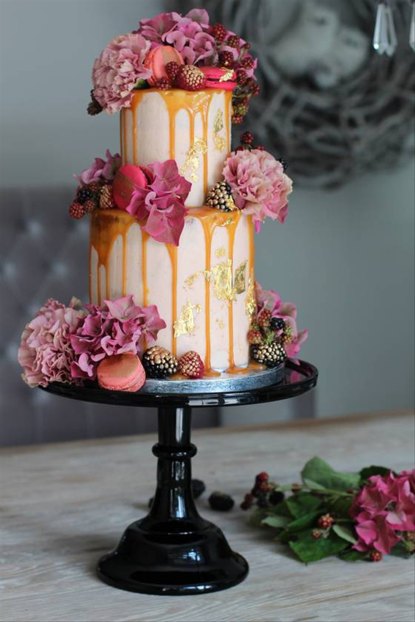 white fondant cake with caramel drip icing, pink flowers, and pink macarons