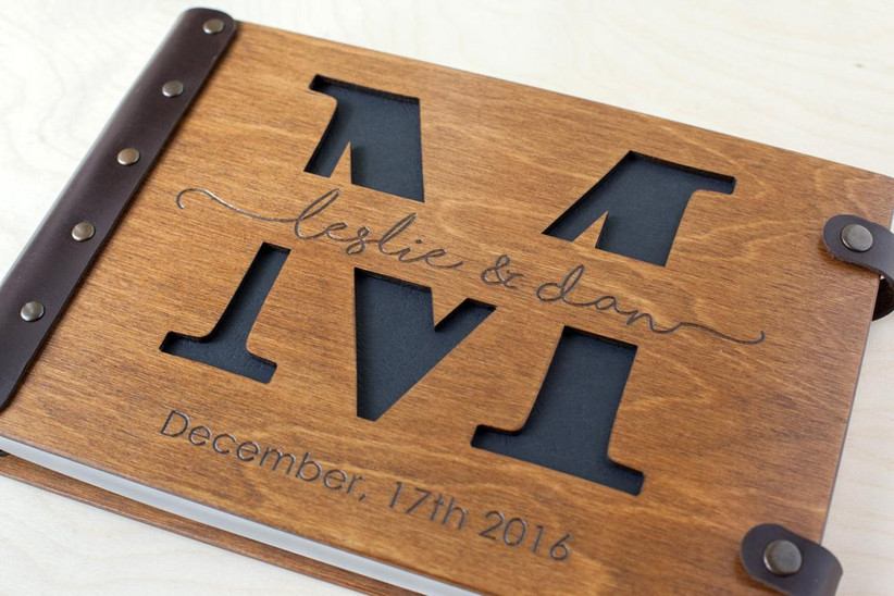 Wood cover wedding photo book engraved with couple's names, wedding date, and monogram