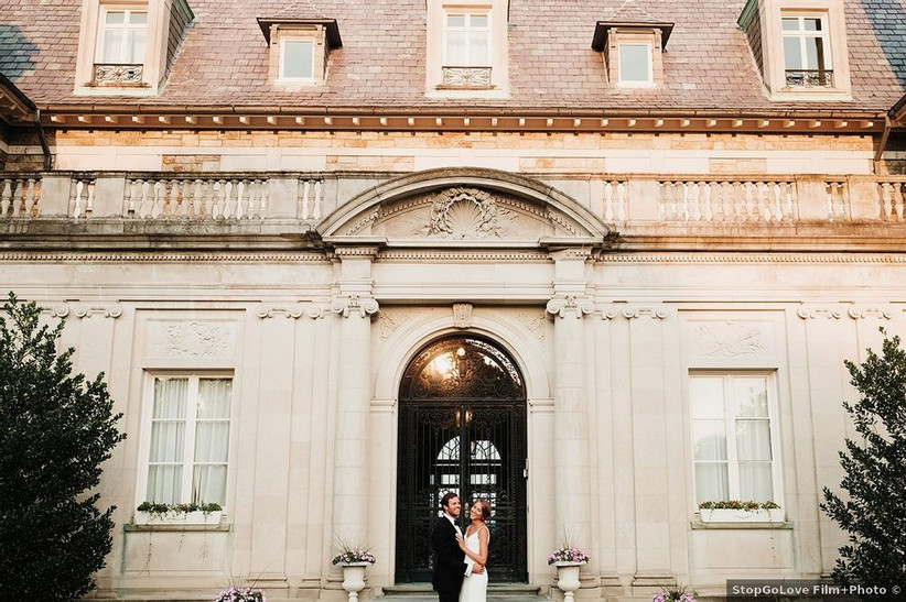 bride and groom standing outside historic home