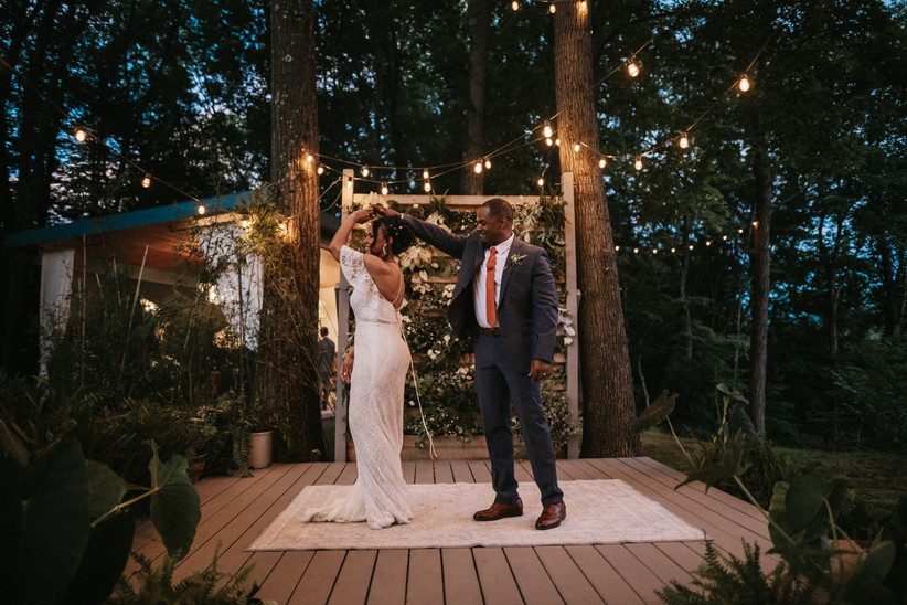 groom twirls bride on wooden platform surrounded by twinkle lights and trees