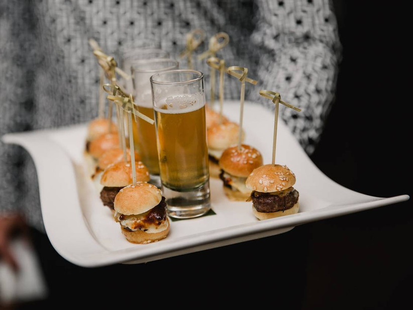 beef sliders on a plate with small glasses of beer