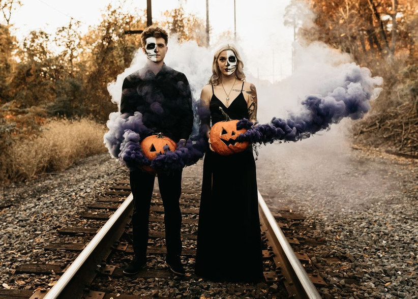 bride and groom with skeleton face paint stand on train tracks holding smoke bomb jack o lanterns