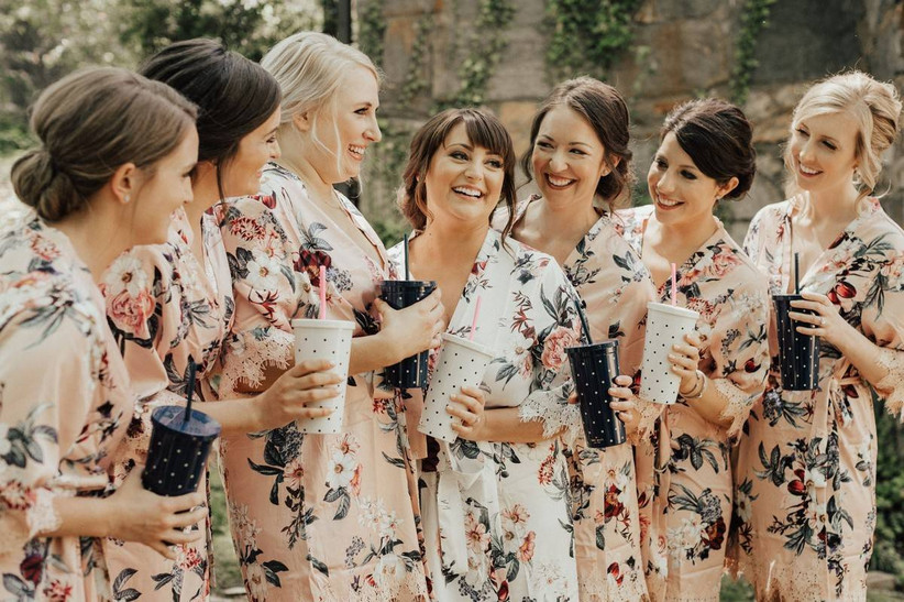 bride and bridesmaids wear matching floral-print robes and hold plastic tumbler cups