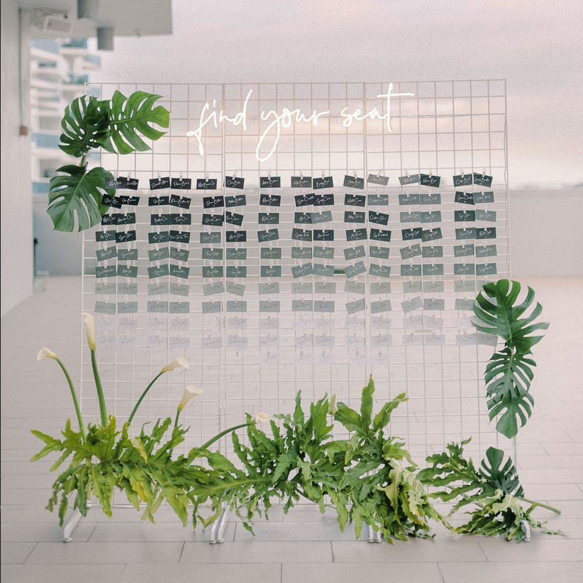 wedding escort card display on metal grid with ombre green cards and tropical greenery