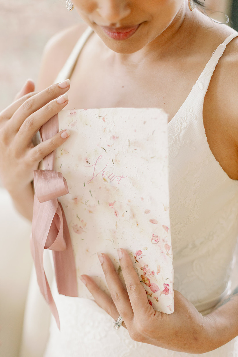 bride holding handmade vow book made from seeded paper with flower petals