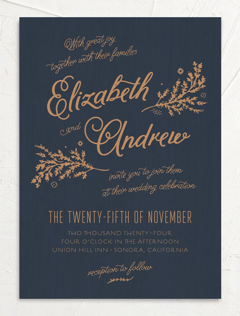 dark blue fall wedding invitation with whimsical gold calligraphy and greenery motifs
