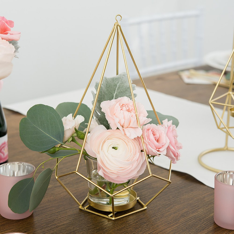 Pink flowers in a glass jar with gold geometric structure as engagement party centerpiece