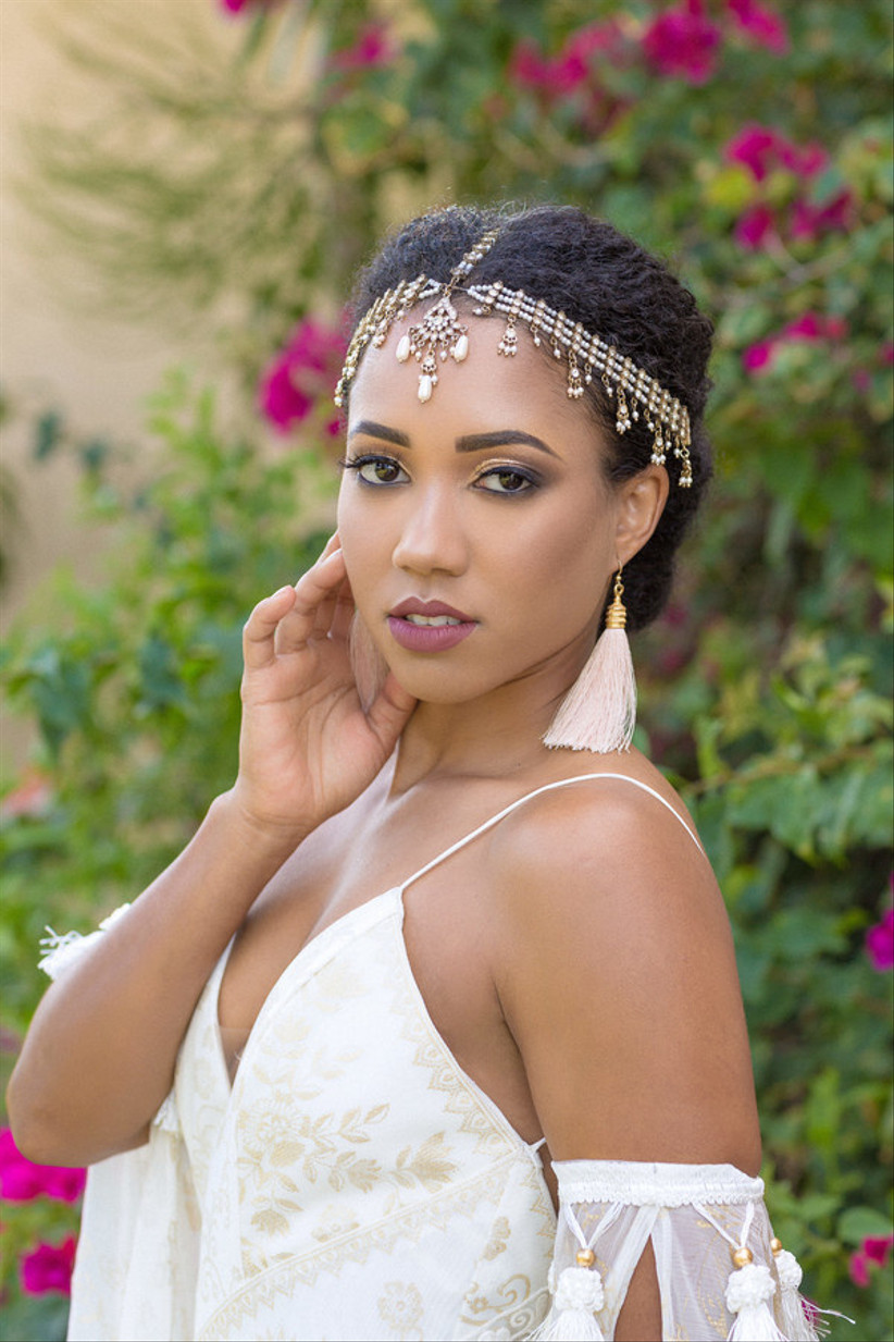 Black bride with kinky hair in a low bun accessorized with gold head chain