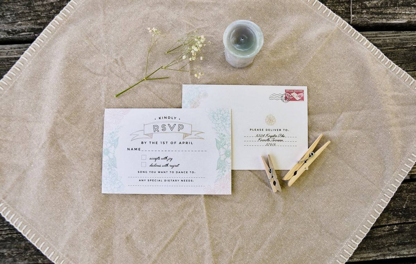 rustic wedding rsvp card placed on a scrap of burlap surrounded by baby's breath, clothespins, and twine