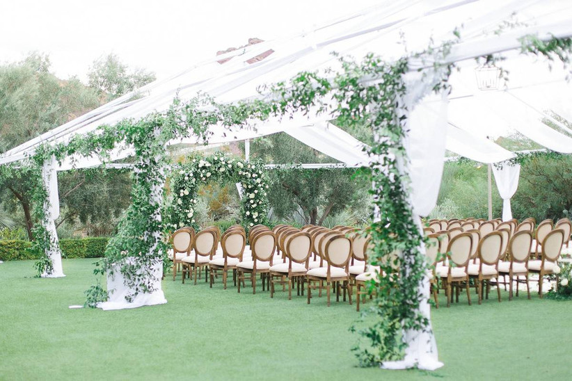 outdoor wedding ceremony chairs arranged in rows under a clear-top wedding tent decorated with greenery garlands along the poles