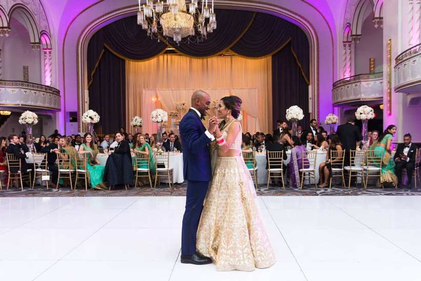 Indian bride and groom during first dance with groom wearing navy blue tuxedo and bride wearing white and gold lehenga