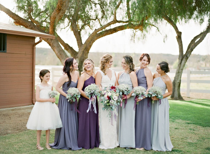 Bride posing with bridesmaids and flower girl with bridesmaids wearing varying hues of blue and purple