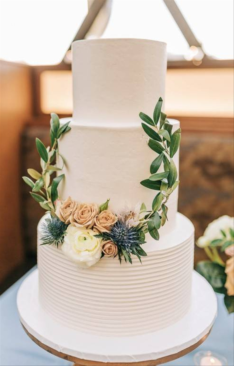 a white wedding cake decorated with small roses and greenery leaves