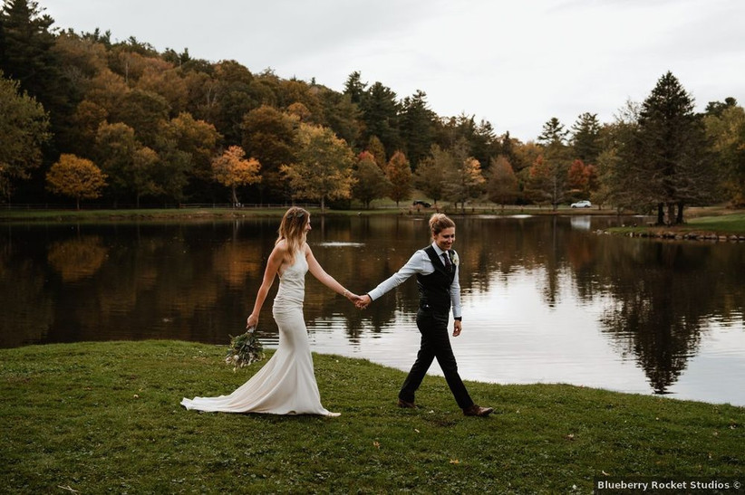 two brides walk hand-in-hand along a lakefront with orange fall foliage in the background