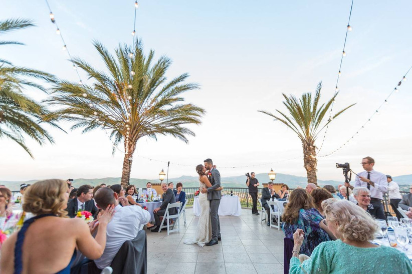 couple kissing during first dance during outdoor reception surrounded by palm trees