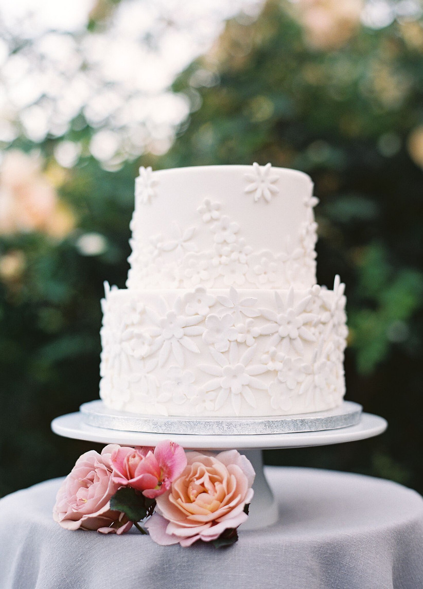 white wedding cake decorated with white three-dimensional flowers made from sugar