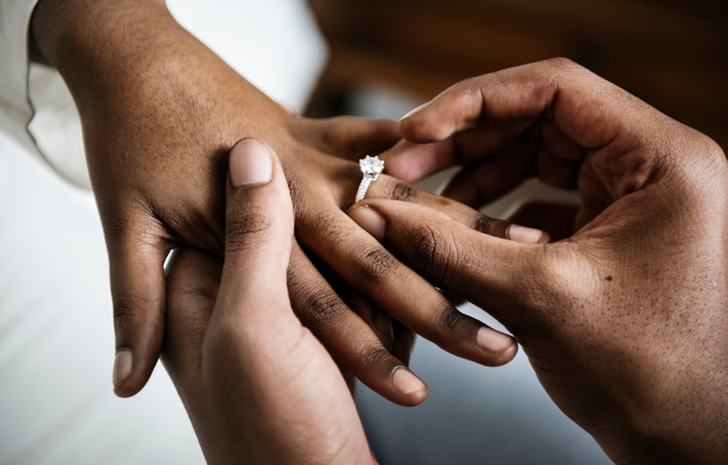 close-up of man placing engagement ring on woman's finger