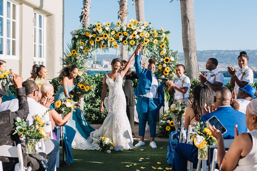 two brides same-sex wedding stand at alter smiling with hands in the air with sunflower ceremony arch and ocean view in the background