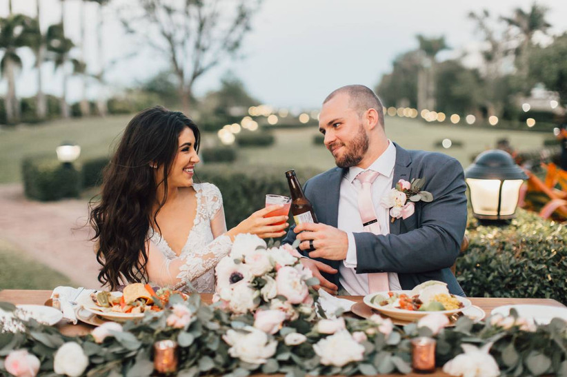 cheers to learning how to plan a wedding like this bride and groom who are toasting at their wedding reception