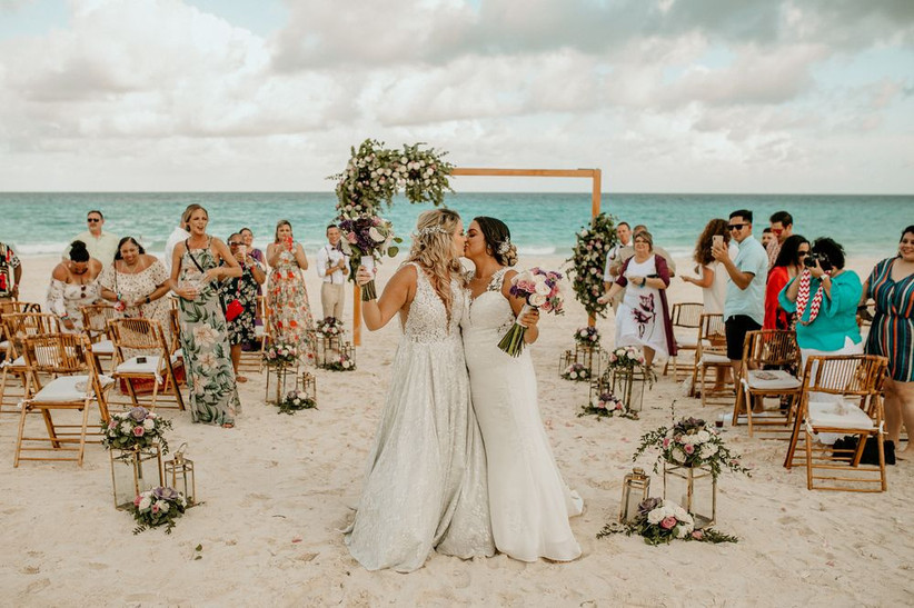 two brides kiss at beach wedding ceremony while guests cheer in the background