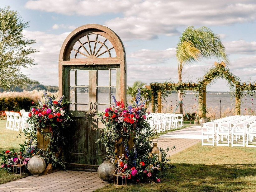 outdoor waterfront ceremony with reclaimed door at the start of the aisle decorated with flowers and vintage lanterns