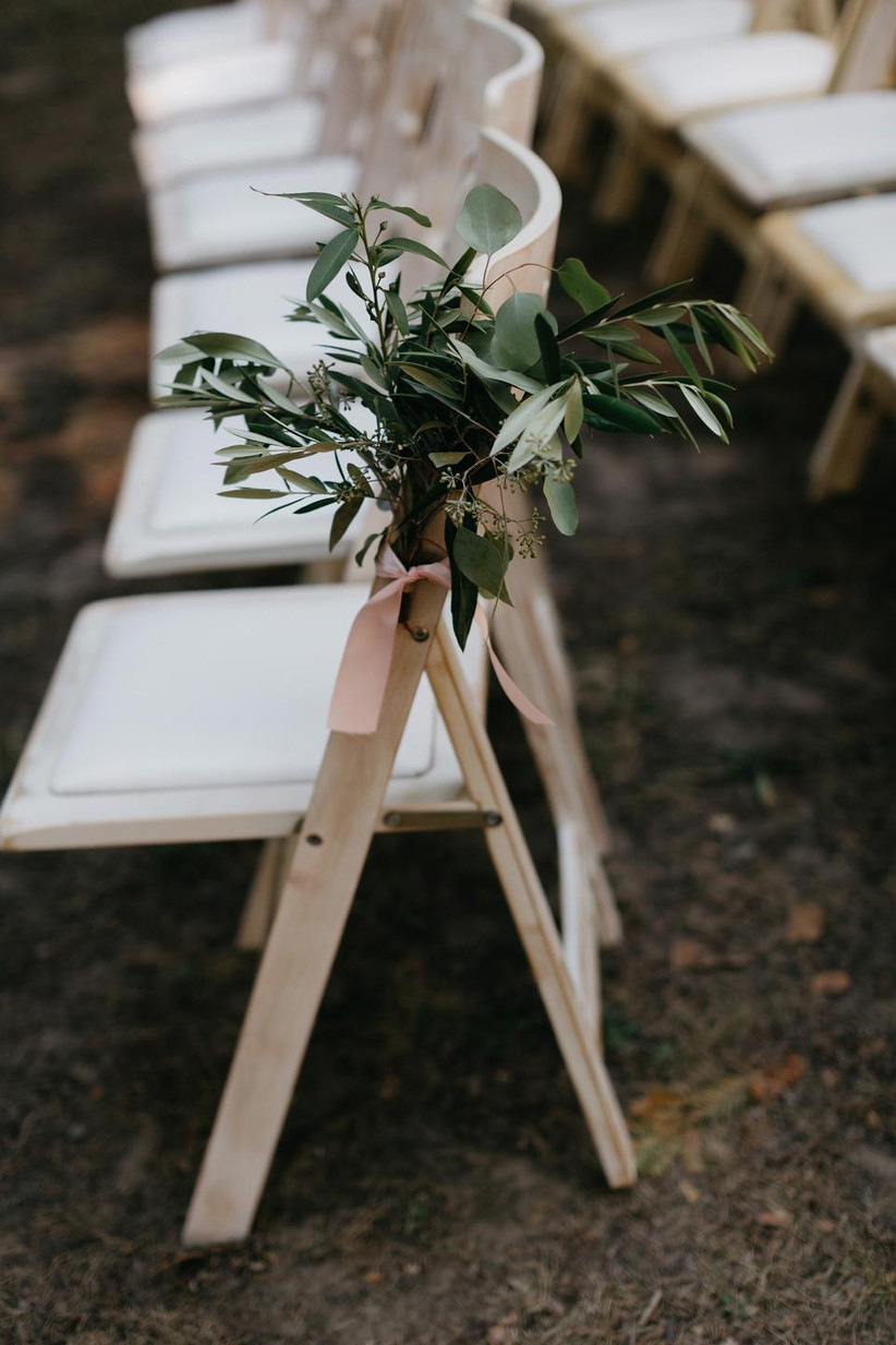 romantic outdoor wedding aisle decor greenery bunch tied to folding chair with blush pink ribbon