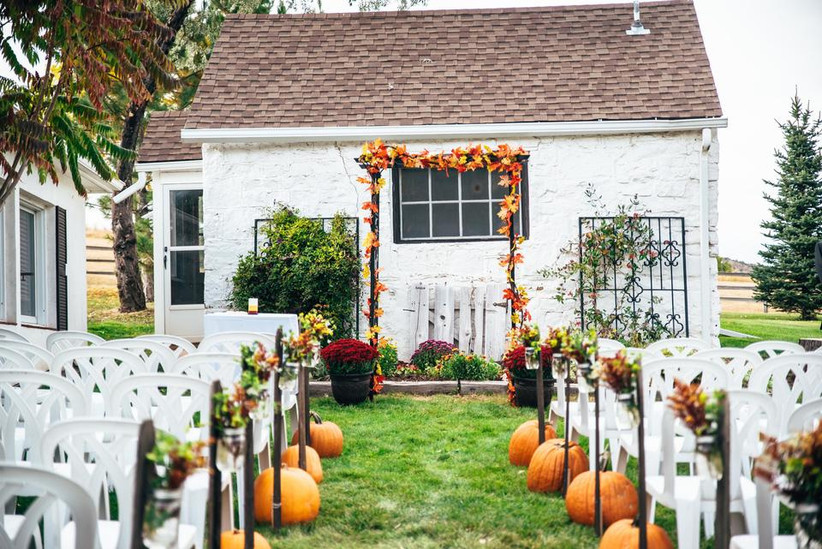 fall outdoor wedding aisle decor pumpkins at the end of each row