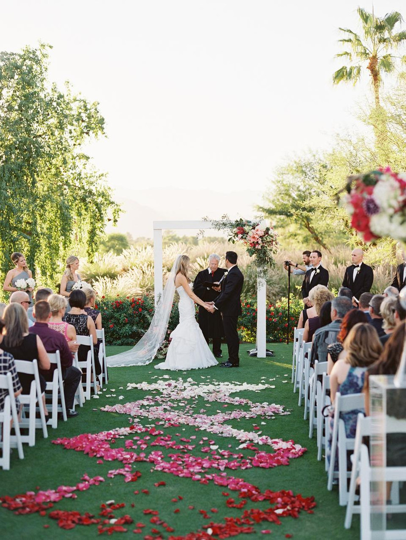 glam outdoor wedding aisle decor ombre pink and red rose petals in swirled pattern down the aisle