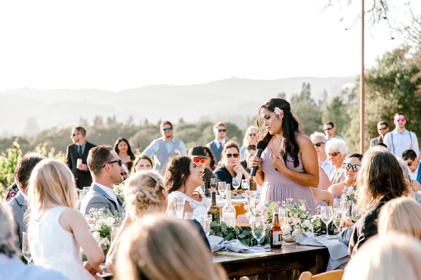 maid of honor giving a toast at an outdoor wedding reception