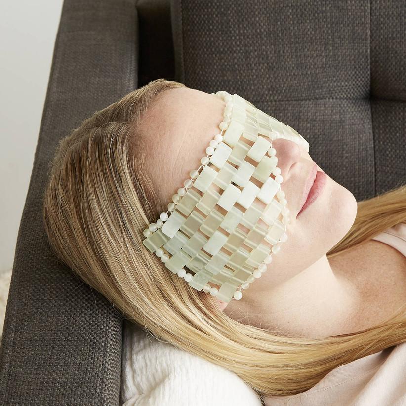 Woman wearing jade gemstone relaxation mask