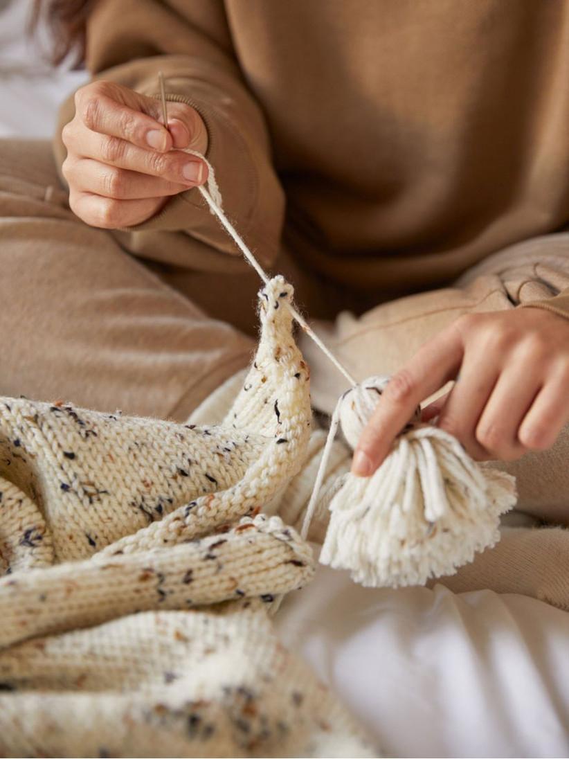 Woman knitting blanket from DIY blanket kit