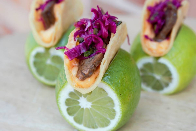 single-bite tacos presented on slices of limes