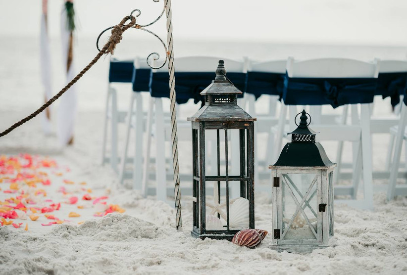 beach wedding ceremony decor with vintage lanterns and seashells as aisle markers