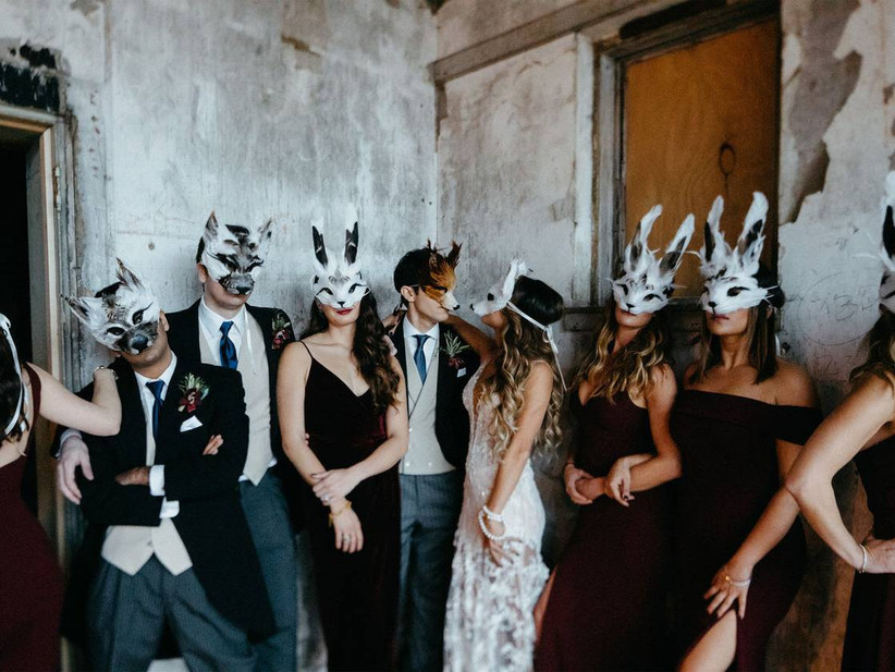 bride and groom stand with their wedding party wearing woodland creature masks