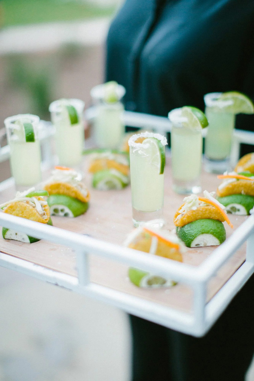 server holds a tray of mini shooters and bite size tacos in lime wedges