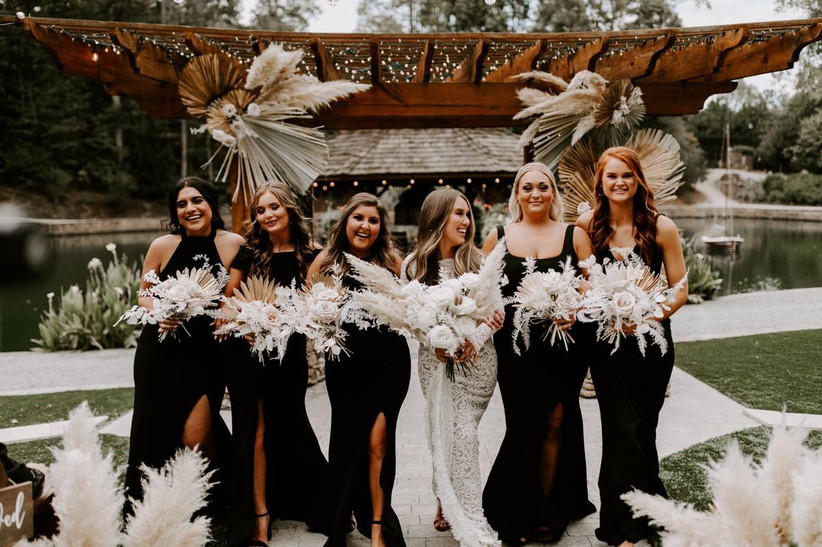 boho bride stands with bridesmaids wearing floor-length black gowns