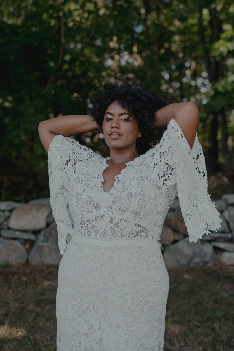 Model wearing lacy boho-style wedding dress