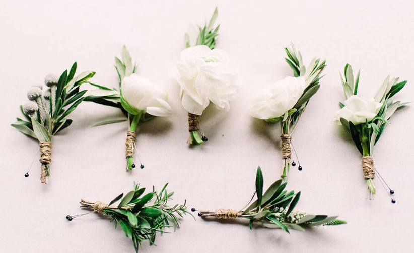 a row of greenery boutonnieres arranged side by side against white backdrop