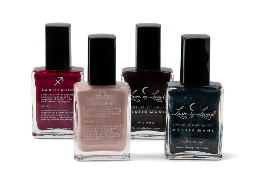 Four zodiac nail polishes in different shades from left to right: red, blush, black, dark blue