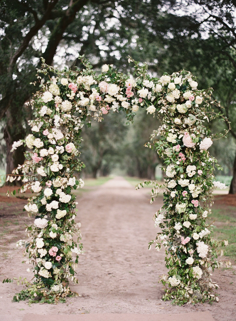 wedding flower arch decorated with blush and white garden roses with greenery