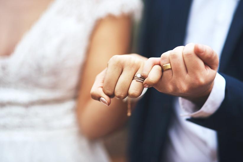 bride and groom with locked pinkies wearing wedding rings