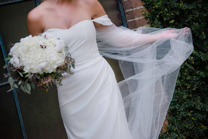 bride wearing a long white veil and carrying a white bouquet