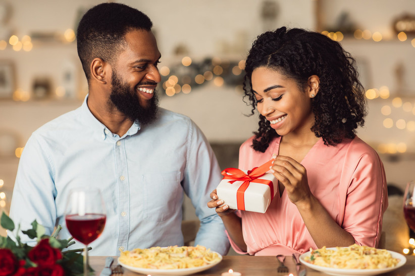 couple sitting at a dinner table woman is opening a gift box with a red ribbon