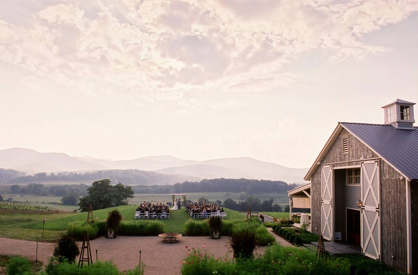 aerial photograph of pippin hill farm in virginia barn on right side of frame with mountains and rolling hills in the distance at sunset