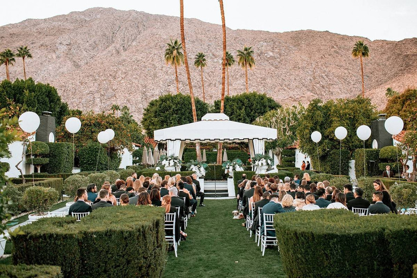 palm springs wedding ceremony with outdoor cabana and white balloons