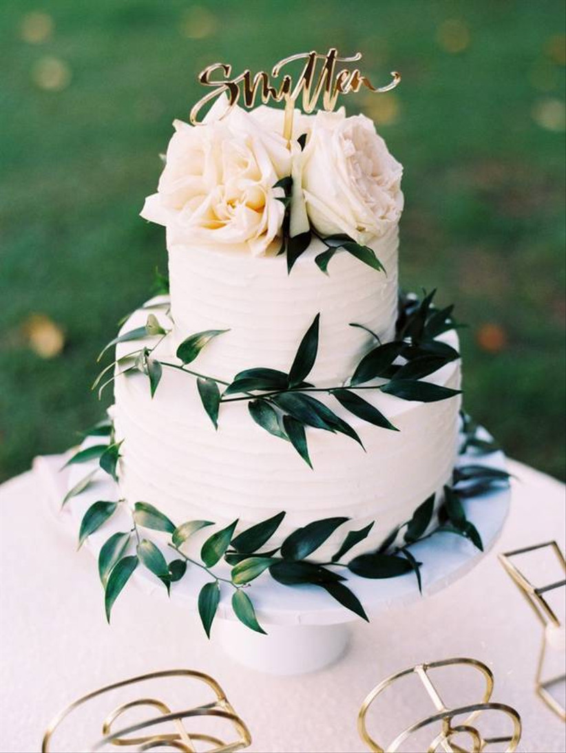 wedding cake decorated with large white roses and greenery vines