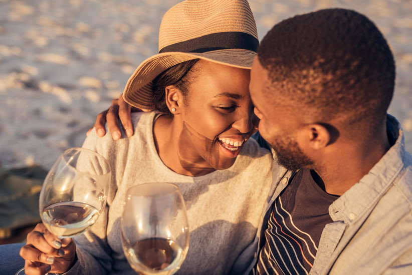newlywed couple on a beach at sunset with wine glasses