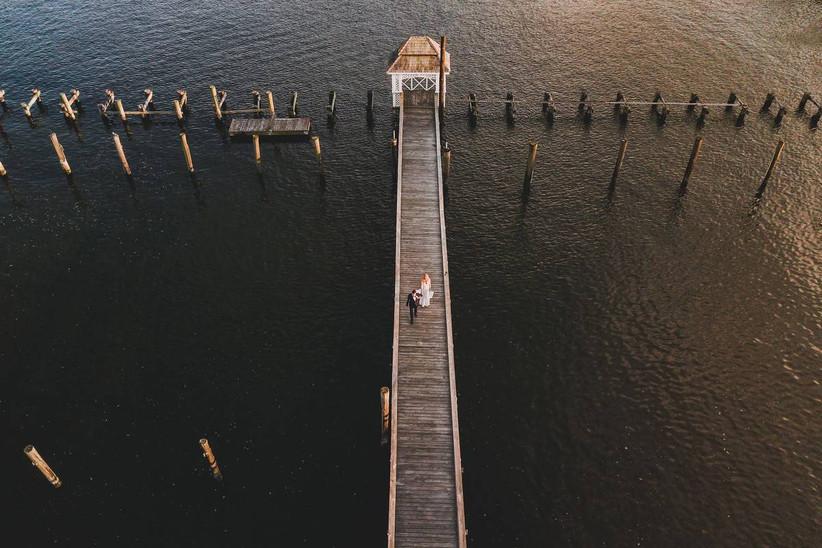 bride and groom walking along pier